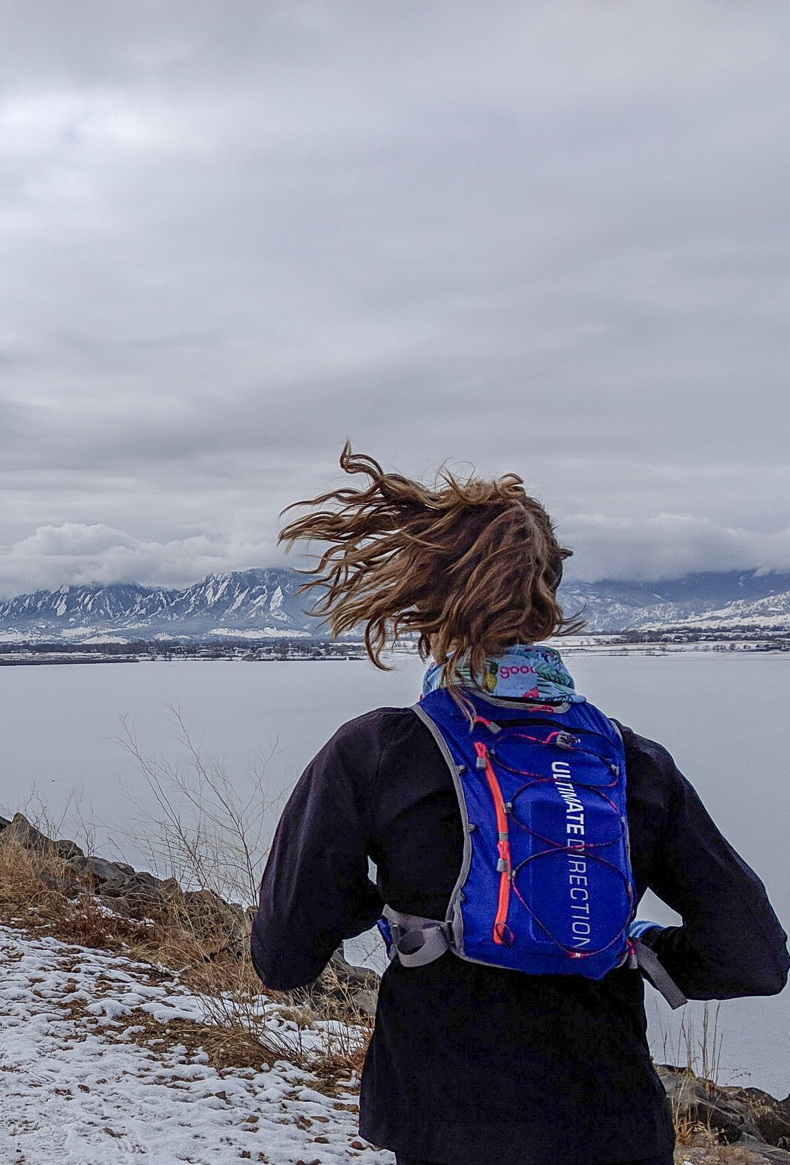 Trailkat running at the frozen over Boulder Reservoir with snowy mountains in the background